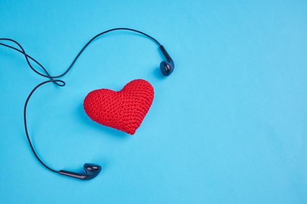 블루 복사 공간에 붉은 마음 근처 검은 이어폰. 음악 리듬 개념에 대한 사랑