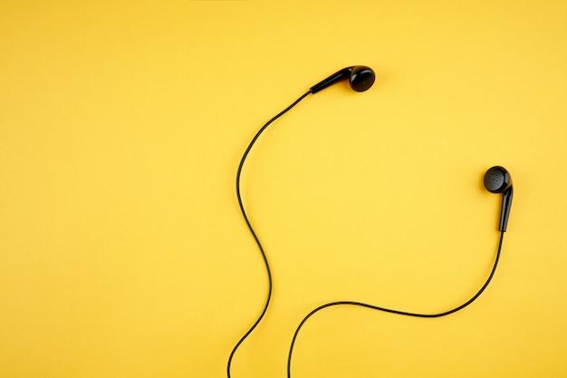 따뜻한 노란색 유행에 검은 이어폰. 음악 라이프 스타일 개념입니다. 복사 공간. 평평하다