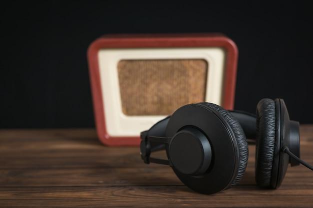 검은색 배경에 나무 테이블에 철사와 복고풍 라디오가 있는 검은색 이어폰. 고대 무선 공학의 개념적 이미지입니다.