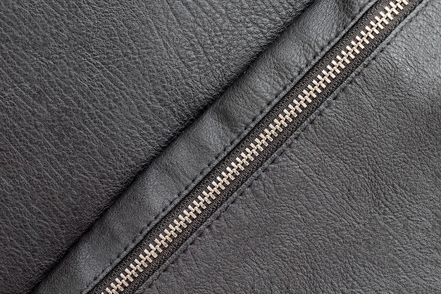 Black eco leather background with closed diagonal zipper