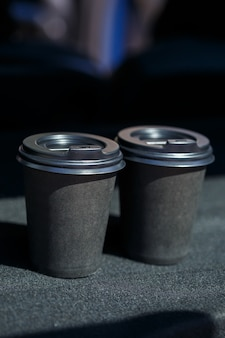 Черные эко бумажные стаканчики для кофе. две чашки горячего чая с крышкой