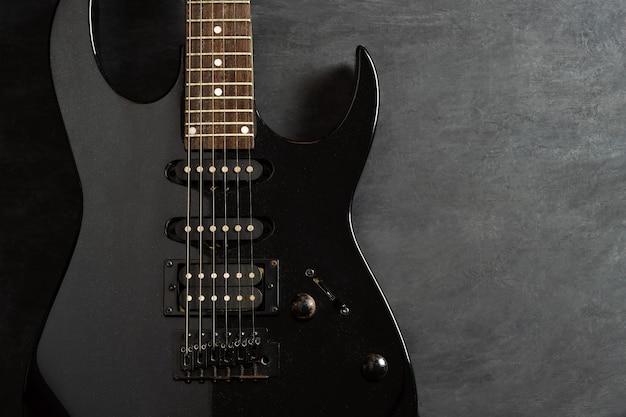 Черная электрогитара на фоне черного цементного пола