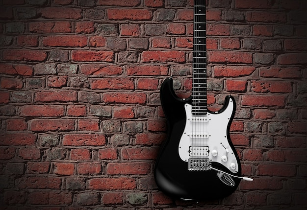 붉은 벽돌 벽의 배경에 검은색 일렉트릭 기타