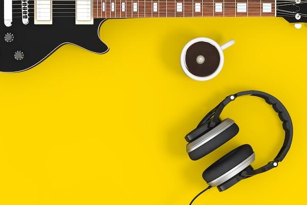 Черная электрогитара с наушниками и чашкой кофе на желтом фоне. 3d рендеринг