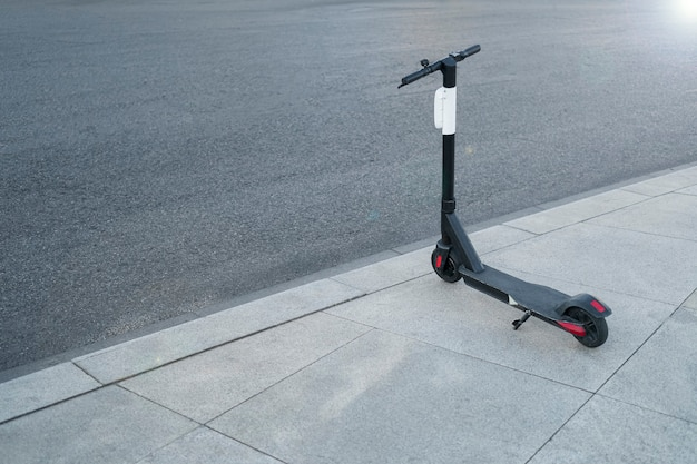 Black electric kick scooter parked in the city. back view. mobility concept