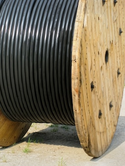 Black electrical wires in plastic coating on wooden spoo