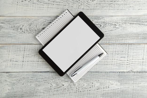 ヴィンテージのぼろぼろの白い木、上面に黒い電子タブレットと紙のノート