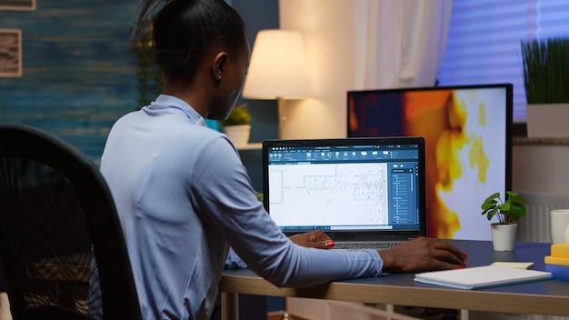 흑인 직원이 밤 늦게 거실 사무실 책상에 앉아 노트북을 보고 있는 회사의 프로젝트를 분석하는 디지털 청사진을 확인합니다. 현대 기술을 사용하는 바쁜 아프리카 프리랜서