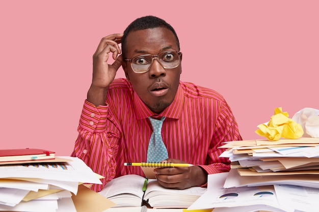 Black employee gazes with stupefaction, has widely opened eyes, wears spectacles, formal pink shirt, makes recordings