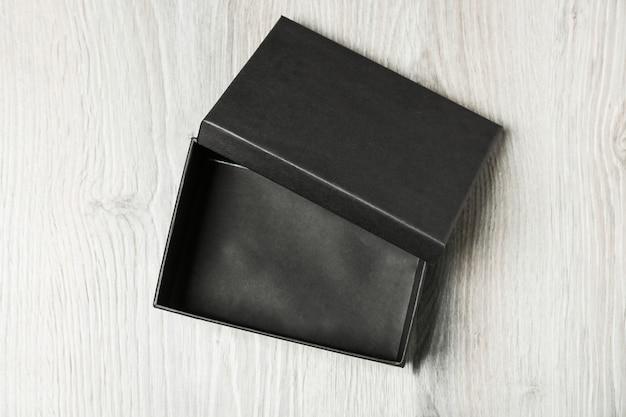 Черная пустая коробка на деревянном фоне
