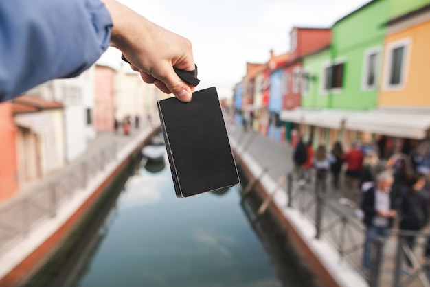 Black empty card in the hands of a young man on colored houses and canal of burano island, venice.