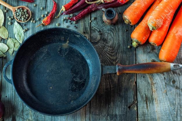 Black empty cast-iron frying pan among vegetables