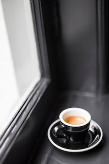 Black empty coffee cup with coffee stains on window sill
