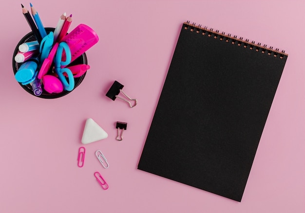 Черный пустой блокнот пустой, красочные канцелярские принадлежности на розовом фоне.