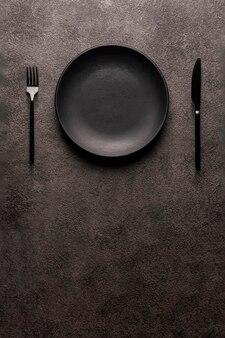 暗い表面に黒い空のプレートとカトラリー、フォークとナイフ