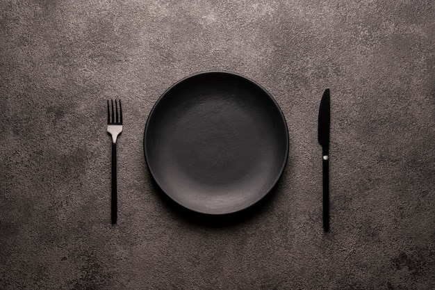 Черная пустая тарелка, вилка и нож для столовых приборов на темном текстурированном фоне, концепция макета для дизайна веб-сайта или дизайна меню ресторана