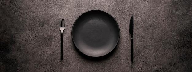 Черная пустая тарелка и столовые приборы, вилка и нож