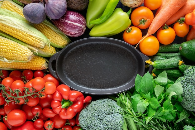 Black empty plate on a background of fresh bright organic vegetables.