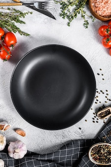 Black empty plate in center of tomatoes and spices