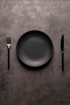 Black empty plate and cutlery, fork and knife on a dark textured background. the concept of a layout for the design of a restaurant menu, website, or design. vertical layout of food photos.