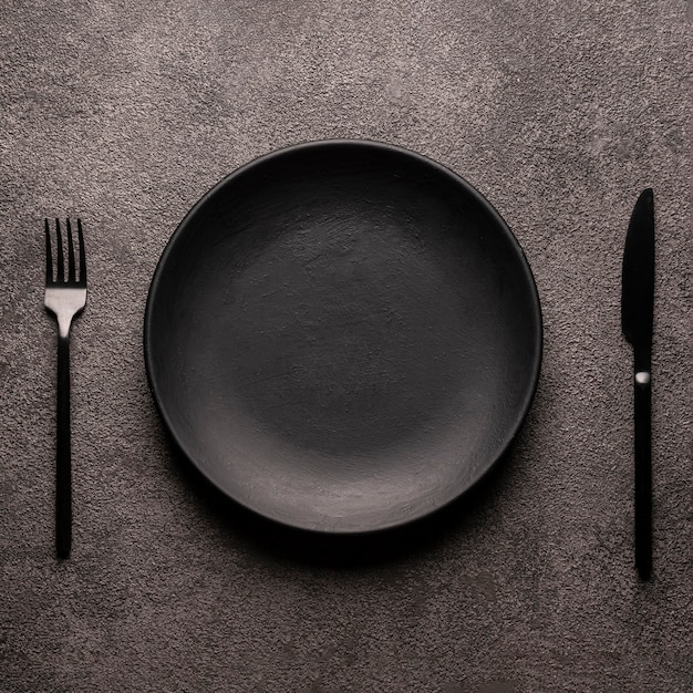 Black empty plate and cutlery, fork and knife, on a dark textured table. concept for the design of a restaurant menu, website or design. square layout