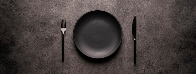 Black empty plate and cutlery, fork and knife