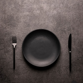 黒の空のプレート、暗いテクスチャのテーブル上のフォークとナイフ、yスペースフラットはミニマリズムの静物を置きました