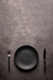 Черная пустая тарелка, вилка и нож на темном текстурированном столе