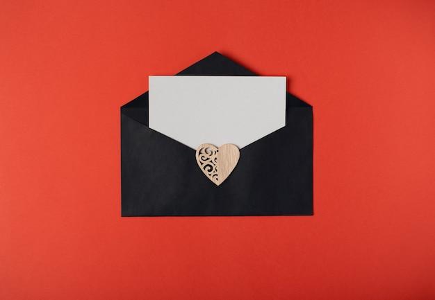 Черный конверт с чистым листом бумаги внутри и деревянным сердцем на нем. концепция дня святого валентина. плоская планировка, вид сверху.