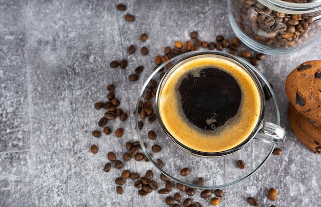 Black espresso coffee in a glass with cream on gray background with scattering of coffee beans. top view, flat lay with copy space.
