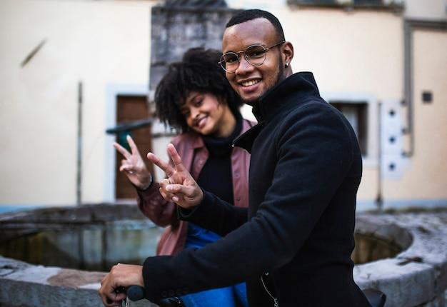 Black ethnic couple doing ok sitting on the bicycle.