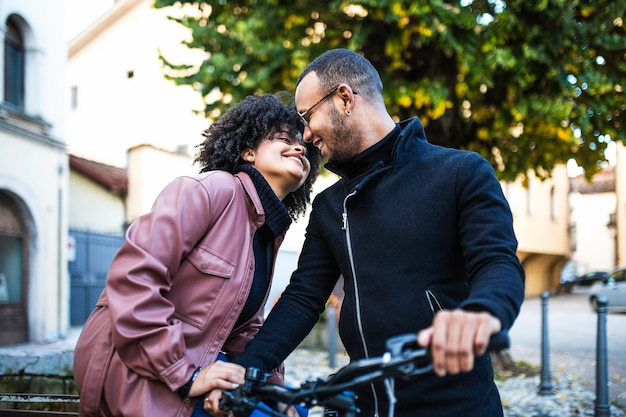 Black ethnic couple love each other. happy young people sitting on bicycle.