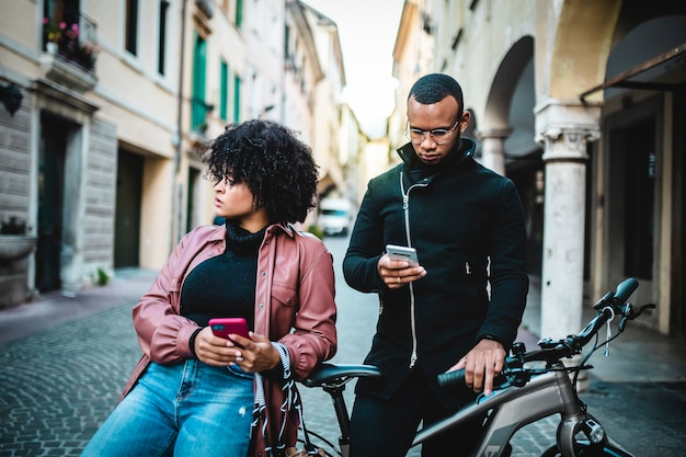 Black ethnic couple with cellphone sitting on bicycle.