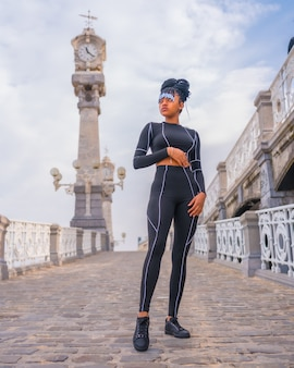 Black ethnic girl with braids with with black full body suit. fashion posã© next to a beautiful beach clock