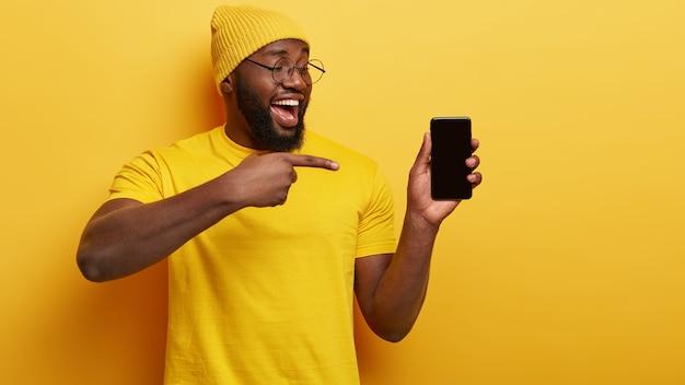 두꺼운 강모를 가진 흑인 민족 남자, 스마트 폰 장치를 가리키고, 홍보 콘텐츠에 빈 화면을 표시하고, 모자를 쓰고, 캐주얼 한 노란색 티셔츠를 입고, 고객에게 새 장치를 광고합니다.