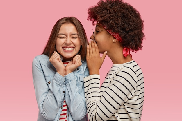 Black ethnic woman whispers secret to her caucasian female with toothy smile, gossip together