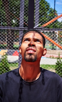 Black ethnicity man looking up at basketball hoop