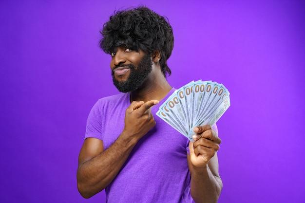 紫色の表面に対してドル紙幣の山を保持している黒人の興奮した男