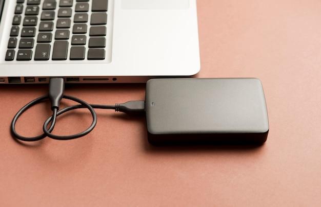 Черный внешний жесткий диск частичный вид ноутбука коричневый фон