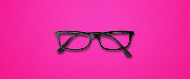 ピンクの背景バナーに分離された黒い眼鏡
