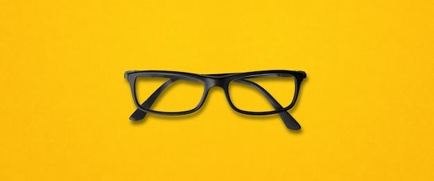 노란색 배경 배너에 고립 된 검은 안경