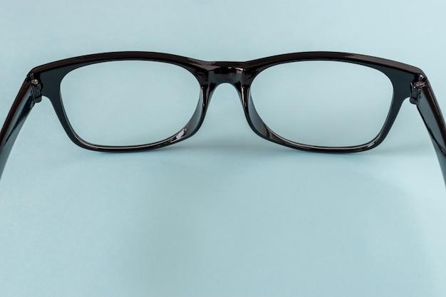 青い背景の上の黒い眼鏡