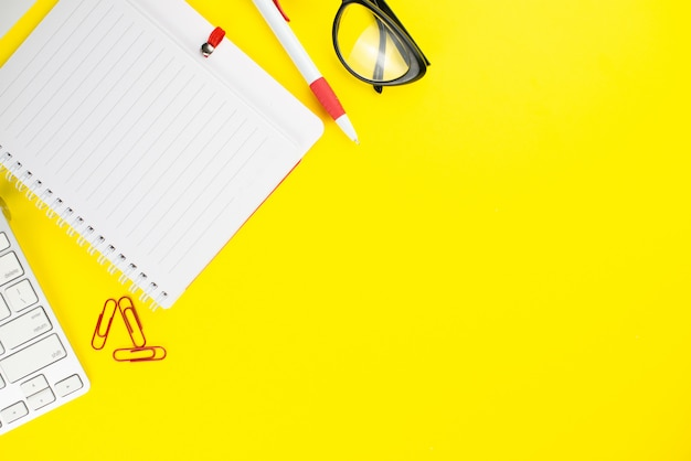 Black eye glasses, pen, keyboard, notepad planner and colorful clips on yellow background.