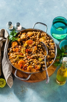 Black-eyed pea vegan chili in a metal pan on a wooden stand on a blue