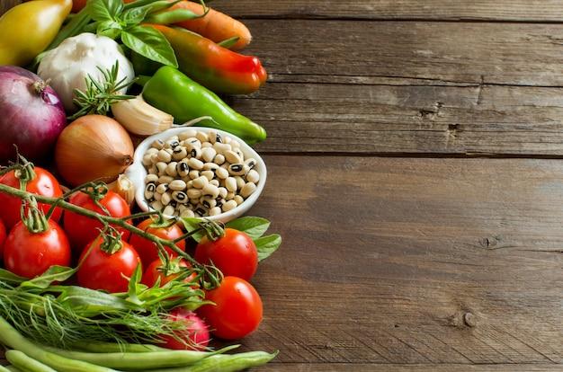 ボウルと野菜で黒い目をしたエンドウ豆はコピースペースを持つ木製のテーブルにクローズアップ