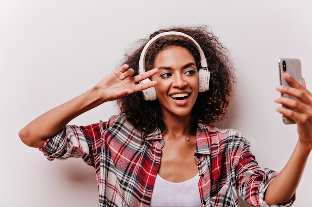 Black-eyed positive woman making selfie with peace sign and laughing. jocund curly girl in big headphones having fun.
