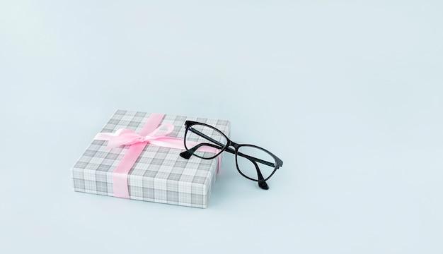 黒の眼鏡と水色の背景にプレゼントボックス