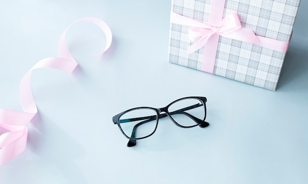 밝은 파란색 배경에 검은 안경 및 선물 상자