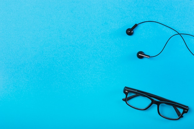 Black eyeglasses and earphone on blue background
