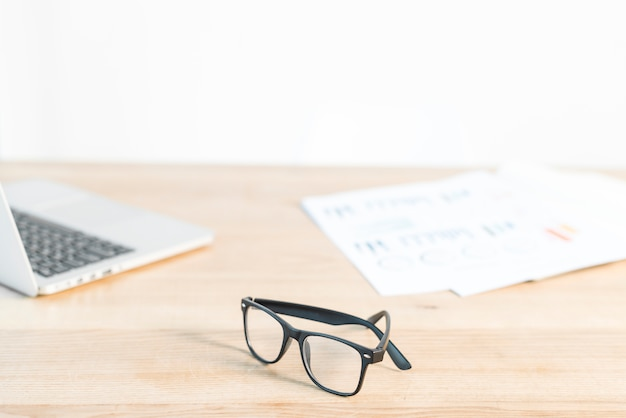 Black eyeglasses in front of laptop and graph on wooden desk